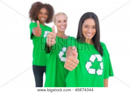 Three smiling environmental activists giving thumbs up in a line on white background