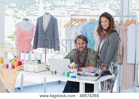 Young fashion designers working in a bright office and smiling to the camera