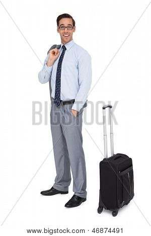 Happy businessman waiting next to his luggage on white background