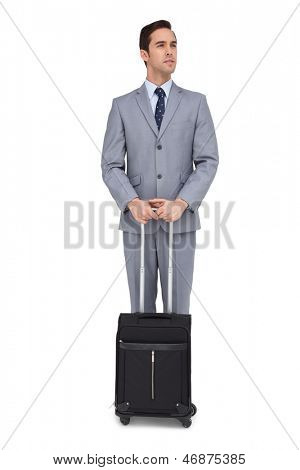 Serious young businessman waiting with his luggage on white background