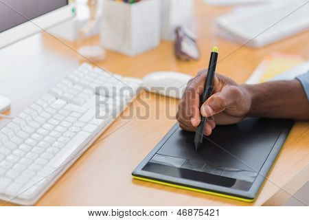 Close up of a graphic designer using graphics tablet in a modern office