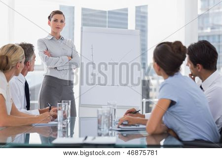 Businesswoman with arms folded in front of a growing chart during a meeting