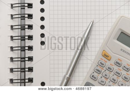 Elegant Silver Pen And Scientific Calculator On White Page Of Spiral Notebook