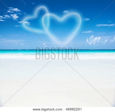 Romantic seaside resort, beautiful seascape, two heart shaped clouds in the blue sky, honeymoon vacation, paradise beach, summer holiday concept