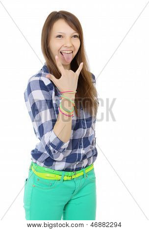 Teenage girl shows tongue and makes hand horns. Mint-colored pants and a plaid shirt. Two belts.