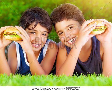 Closeup retrato de dois meninos felizes comendo grandes saborosos hambúrgueres gordurosos ao ar livre, deitado no verde fiel
