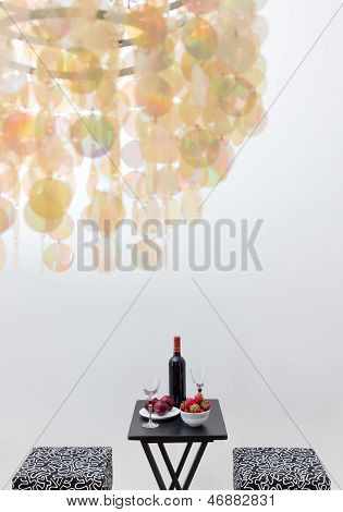 Bottle Of Red Wine On A Table, And Decorative Chandelier