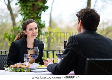 Businesspeople having business lunch outside on the terrace in a fine dining restaurant