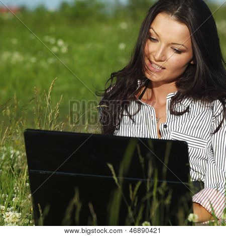 girl with laptop on green grass