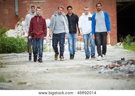 Portrait of spiteful hooligans walking down street