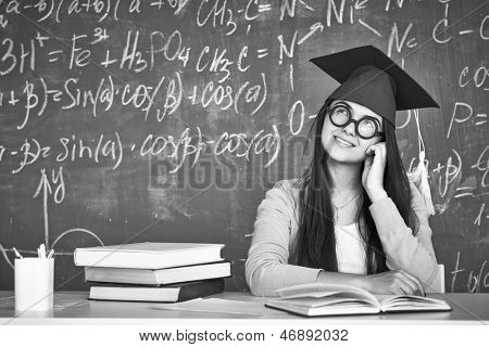 Black-and-white image of pensive student in graduation hat and eyeglasses on background of chalkboard