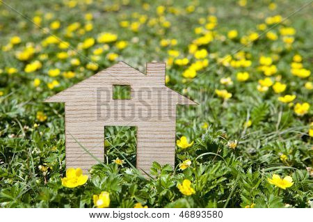 Wooden model house in green field