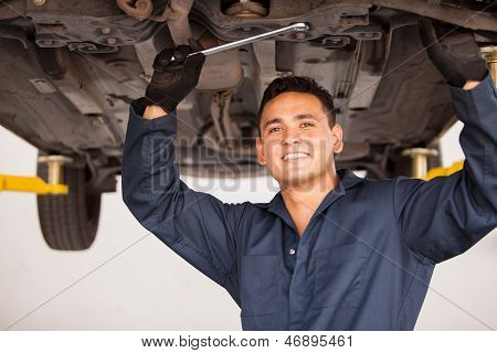 Happy mechanic working on a car