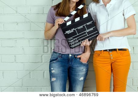 Two Young Girls Holding A Clapboard