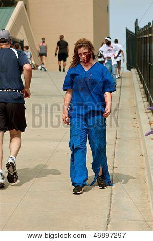 Female Zombie Nurse Skulks After Runners In 5K Run