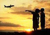 Two kids silhouette on meadow looking at airplane in air