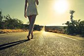 stock photo of sun god  - young woman walking barefoot on a long deserted road - JPG