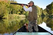 stock photo of hunt-shotgun  - hunter in boat - JPG