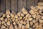 stock photo of log fence  - Pile of firewood against old wooden fence - JPG