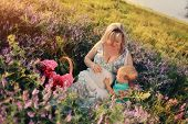 stock photo of wildflowers  - Summer walk on the field with wildflowers pregnant mother with a young son - JPG