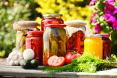 stock photo of vinegar  - Jars of pickled vegetables in the garden. Marinated food