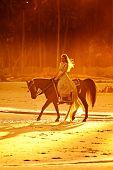stock photo of bareback  - woman in medieval dress riding horse on beach at sunset - JPG