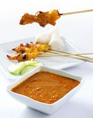 Chicken satay, grilled and skewered meat, served with peanut sauce, cucumber and ketupat. Traditiona