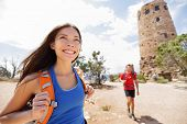 Hiking woman in grand canyon. Female hiker smiling happy with boyfriend in background during hike tr