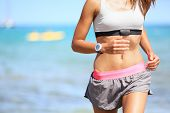 stock photo of exercise  - Runner woman with heart rate monitor running on beach with watch and sports bra top - JPG