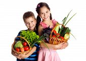 stock photo of green onion  - Smiling kids with fresh vegetables in baskets - JPG