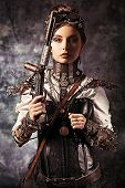 stock photo of gothic female  - Portrait of a beautiful steampunk woman holding a gun over grunge background - JPG