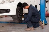 stock photo of overalls  - Young mechanic rotating tires of a suspended car at an auto shop - JPG