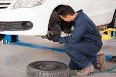stock photo of overalls  - Young mechanic fixing the brakes of a car at an auto shop - JPG