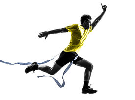 stock photo of sprinters  - one caucasian man young sprinter runner running  winner at finish line  in silhouette studio  on white background - JPG