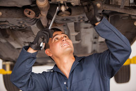 stock photo of suspenders  - Latin young mechanic working on a suspended car at an auto shop - JPG