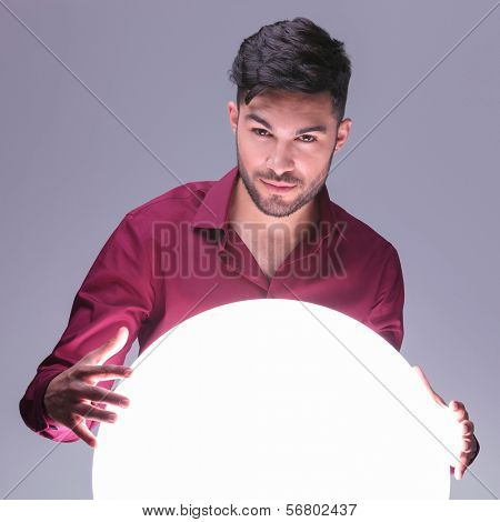 casual man acting as a fortune teller with his big ball of light