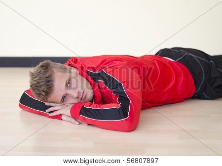 Attractive Young Man Laying On The Floor Wearing Gym Suit