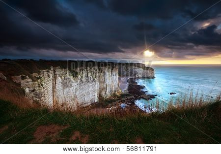 Sunshine And Storm Sky Over Cliffs In Ocean