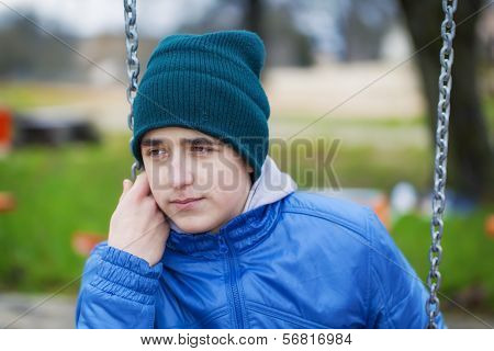 Sorrowful teenage boy swinging in the park