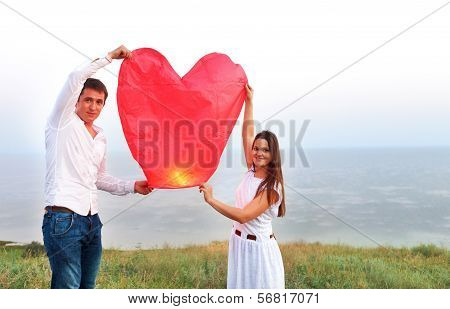 Young Couple Start A Red Chinese Sky Lantern