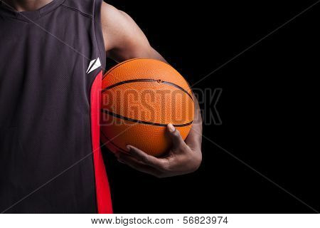Image of a basketball player holding a ball against dark background