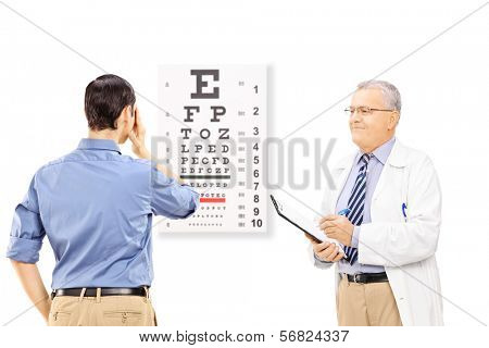 Young male patient taking eyesight test and an optician holding a clipboard, isolated on white background