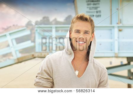 Outdoor portrait of young handsome man with big smile at the beach
