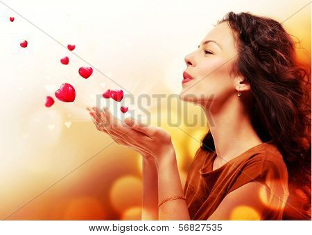 Beauty Young Woman Blowing Hearts from her Hands. St. Valentines Day Concept. Beautiful Girl in Love. Valentine art design. Valentines Gift