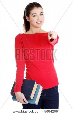 Student woman holding books and pointing on you. Isolated on white