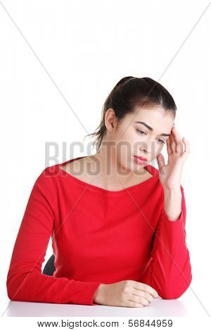 Girl sitting with resigned position. Bored young woman touching her head. Isolated on white background.