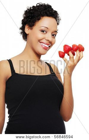Young happy pregnant afro american woman with strawberries, isolated on white background