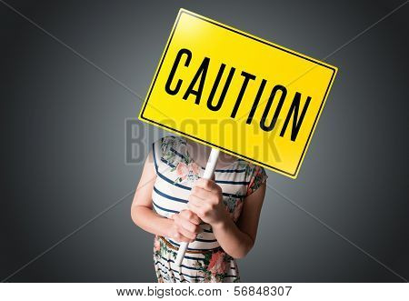 Young lady standing and holding a yellow caution sign in front of her head