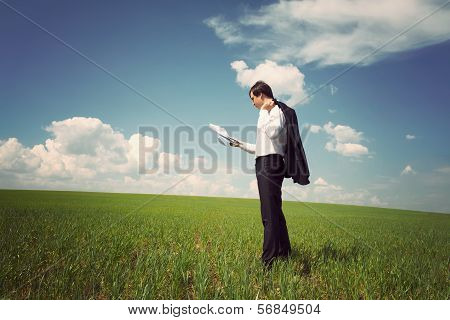 Businessman Standing On A Field With A Blue Sky And Reads The Newspaper Or Documents