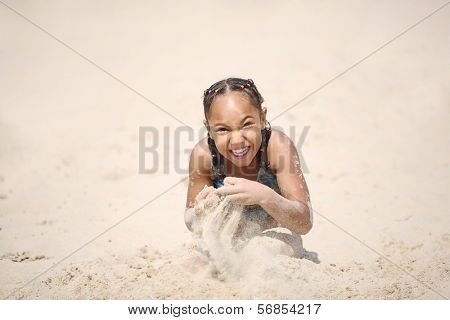Happy girl playing on the beach in the sand
